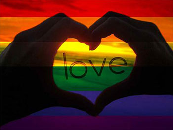 "Silhouette of two hands forming a heart around the word ""love"" over a rainbow background."